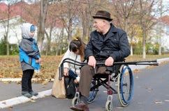 Femme et son fils aidant un vieil homme handicapé Photographie stock