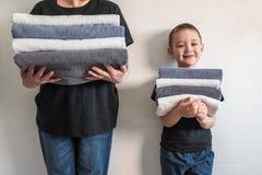 Femme et un garçon tenant les murs proches, tenant des piles de différentes serviettes Concept de la famille Photographie stock libre de droits