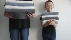 Femme et un garçon tenant les murs proches, tenant des piles de différentes serviettes Concept de la famille clips vidéos