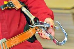 Femme et un harnais de protection de chute Photographie stock
