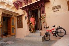 Femme et un vélo moderne dans une maison traditionnelle à Jodhpur Photos stock