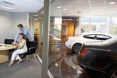 Femme et vendeur s'asseyant dans le bureau de salle d'exposition de voiture Photographie stock libre de droits