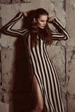 Femme européenne de beaux cheveux bruns dans la pose de robe élégante de colorfull Photos stock