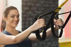 Femme exécutant la formation de TRX dans le gymnase photo stock
