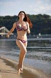Femme exécutant par la plage de fleuve Photo libre de droits