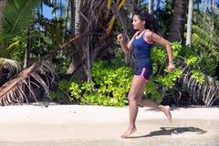 Femme exécutant sur la plage de mer Photographie stock libre de droits