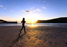 Femme exécutant sur une plage pendant le coucher du soleil Images libres de droits