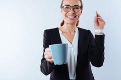 Femme exaltée gaie tenant une tasse avec du café Image libre de droits