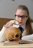 Femme examinant un crâne humain Photographie stock