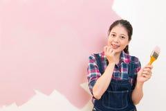 Femme excitée appliquant la peinture rose photographie stock