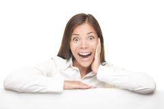 Femme Excited s'appuyant sur le panneau blanc vide Photos libres de droits
