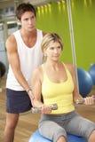 Femme exerçant être encouragé par l'entraîneur personnel In Gym photographie stock libre de droits
