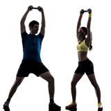 Femme exerçant la formation de poids de forme physique avec le silhouet d'entraîneur de l'homme Photo stock