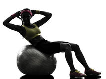 Femme exerçant la silhouette de séance d'entraînement de boule de forme physique de craquements Photo stock