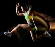 Femme exer?ant l'effet lightpainting de fond noir d'isolement par exercices de forme physique photo libre de droits