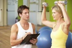 Femme exerçant être encouragé par l'entraîneur personnel In Gym Photos stock