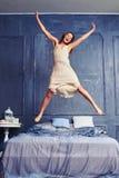 Femme extrêmement enthousiaste dans la chemise de nuit sautant sur le lit avec des bras Photo libre de droits