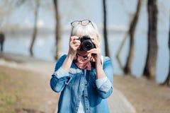 Femme exubérante prenant des photos en parc Image stock
