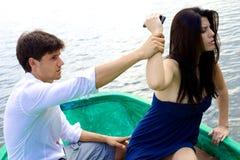 Femme fâchée avec l'ami voulant jeter le téléphone dans l'eau Images stock