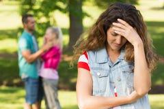 Femme fâchée avec l'homme et l'amie à l'arrière-plan au parc Images stock