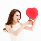 Femme fâchée coupant la forme de coeur par des ciseaux Image stock