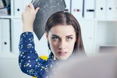 Femme fâchée d'affaires avec le dossier essayant de frapper son collègue dans le bureau Situations stressantes au travail photo libre de droits