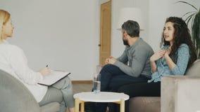 Femme fâchée discutant et parlant de son mari au conseiller de mariage Jeunes couples rendant visite au psychologue professionnel banque de vidéos