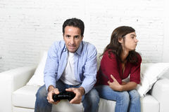 Femme fâchée et bouleversée tandis que le mari ou l'ami joue des jeux vidéo l'ignorant Images stock