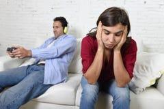 Femme fâchée et bouleversée tandis que le mari ou l'ami joue des jeux vidéo l'ignorant Photo stock