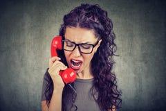 Femme fâchée hurlant au téléphone Photos stock
