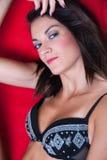 Femme féminine s'asseyant sur la lingerie de port de chaise rouge Photographie stock libre de droits