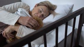 Femme faible se trouvant sur le lit de malade dans l'hôpital étreignant le jouet-ours, espoir pour le rétablissement clips vidéos