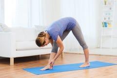 Femme faisant à yoga la pose intense de bout droit sur le tapis photographie stock