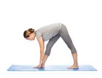 Femme faisant à yoga la pose intense de bout droit sur le tapis Photos libres de droits