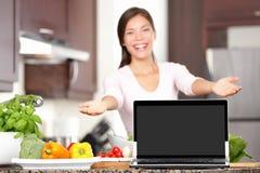 Femme faisant cuire affichant l'ordinateur portatif dans la cuisine Images libres de droits