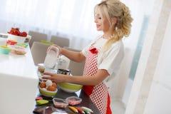 Femme faisant cuire au four à la maison Photos stock