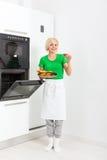 Femme faisant cuire des biscuits de goût faisant le plateau cuire au four de four Images libres de droits