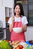 Femme faisant cuire et battant des oeufs dans une cuvette dans la chambre de cuisine Photo libre de droits