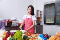 Femme faisant cuire et battant des oeufs dans une cuvette dans la chambre de cuisine Photos libres de droits