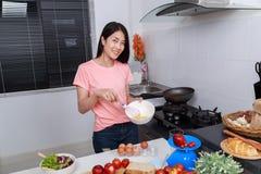 Femme faisant cuire et battant des oeufs dans une cuvette dans la cuisine Photo stock