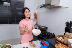Femme faisant cuire et battant des oeufs dans une cuvette dans la cuisine Image stock