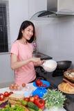 Femme faisant cuire et battant des oeufs dans une cuvette dans la cuisine Images libres de droits