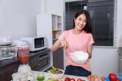 Femme faisant cuire et battant des oeufs dans une cuvette dans la cuisine Photographie stock libre de droits