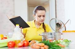 Femme faisant cuire la nourriture de veggie avec le livre de cuisine Photo libre de droits