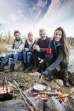 Femme faisant cuire la nourriture sur le feu de camp avec des amis à au bord du lac Photos libres de droits