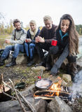 Femme faisant cuire la nourriture sur le feu de camp avec des amis à l'arrière-plan Photographie stock libre de droits
