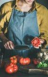 Femme faisant cuire la sauce tomate ou les pâtes au comptoir de cuisine photo libre de droits