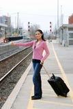 Femme faisant de l'auto-stop à la gare de chemin de fer Photo libre de droits