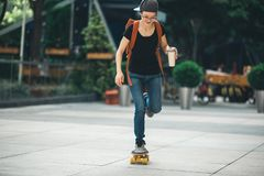 Femme faisant de la planche à roulettes avec la tasse de café photos stock