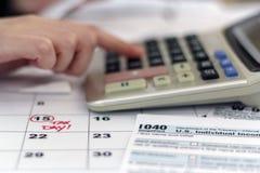 Femme faisant des écritures pour payer des impôts photographie stock